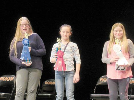 Michelle Jury, Grace Elverud and Elizabeth Cunningham, from left, pose with their spelling bee trophies.