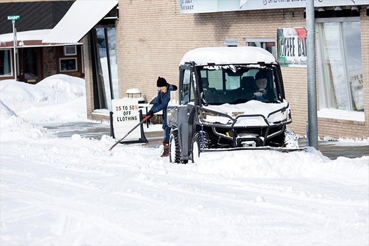People work to remove snow from the sidewalks and streets of downtown Polson last week. Ten inches of snow fell between Sunday, Feb. 24 and Tuesday, Feb. 26.