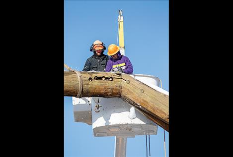 : Sackett and Robert Jennison of Jennison Tree Service clear snow off the arch before loosening the bolts.