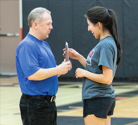 Mission's Karolyna Buck accepts an award from Steve Woll for winning the girls' three-point competition.