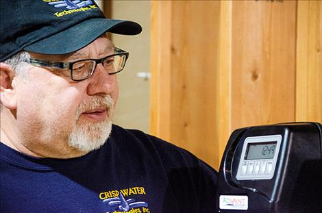 Certified Water Specialist Ken Crisp looks at the arsenic filtration system he set up in Tom Vaughn's home.