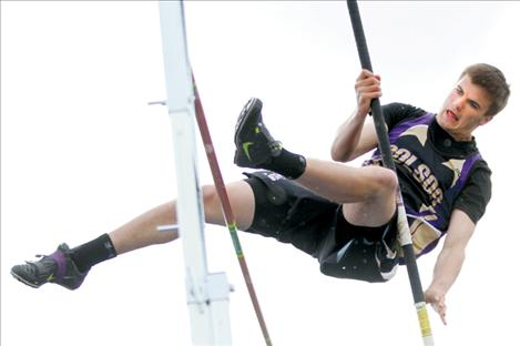 Dylan Kelley concentrates as he clears the bar in pole vault.