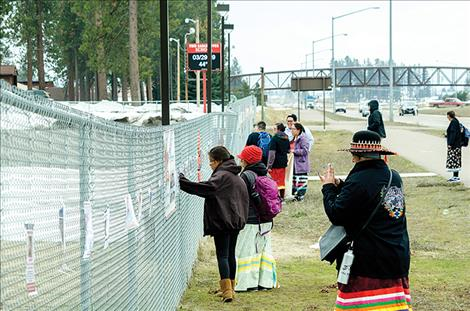Marita Growing Thunder and a group of walkers look at the photos of MMIW displayed on the fence at Two Eagle River School.