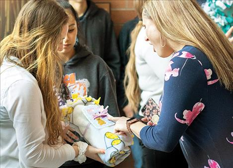 Charlo freshman class president Molly Kate Sullivan shares a finished blanket with St. Luke Community Healthcare marketing manager Brooke Duty.