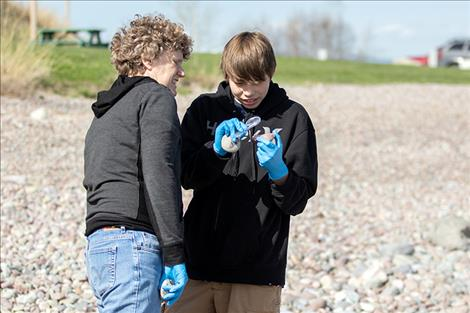Teacher Kathy Fewlass and student Zeke Old Person study a rock as they look for aquatic invasive  species.