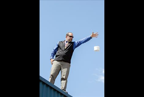 Pablo Elementary principal Mr. Fisher drops one of the students' egg  projects from the school roof.