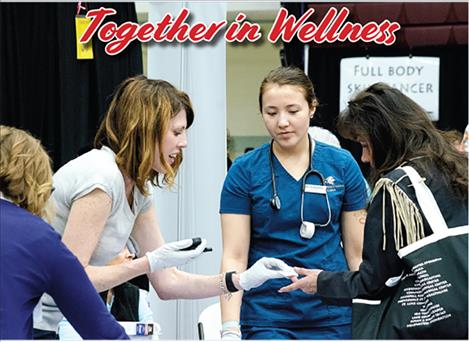 Dr. Hayley Miller with Community Medical Center provides diabetes screening tests during the Women 4 Wellness health fair.