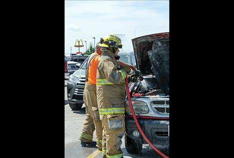 Ronan Volunteer firefighters respond to a car fire in the Ronan Harvest Foods parking lot.