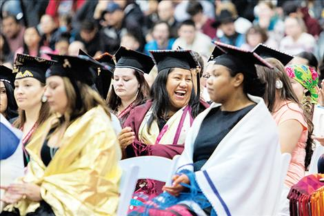 In a sea of serious faces, one graduate lights up the row with a smile.