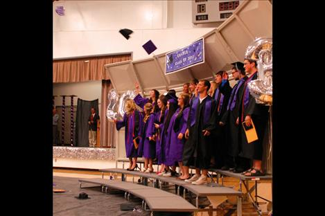 In celebration, graduates of Charlo High School's class of 2013 toss their graduation caps.