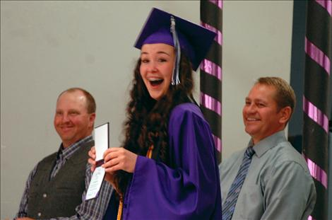 Charlo graduate Derika Stipe shows surprise as her brother Chico pops out to photograph her as she receives her diploma. In the background are school board chair Shane Reum and Charlo Superintendent Thom Peck.