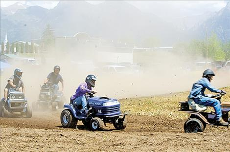 Dirt flies at the lawnmower races as six competitors race for bragging rights.