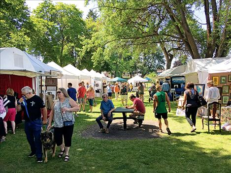 Trees along the shore of Flathead lake keep passersby shaded while browsing art in the afternoon sunshine.