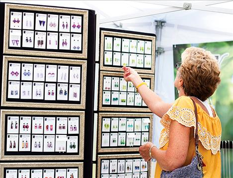 Festival goers browse jewelry  among other custom artwork.