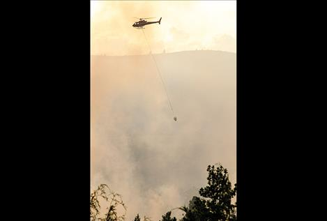 A helicopter helps fight the fire.