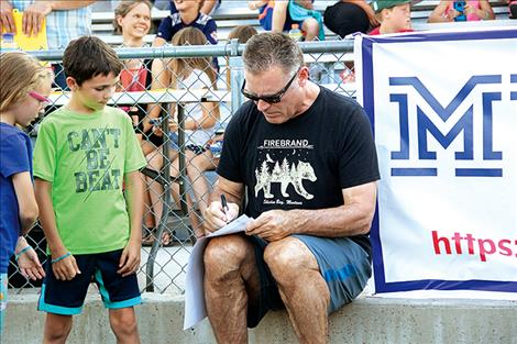 NFL Hall of Famer and Super Bowl Champion Oakland Raider Howie Long signs a few autographs for young fans. Long was the surprise guest at last week's meet-and-greet barbeque event.