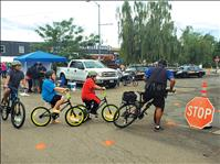 Police officers distribute bicycle safety helmets to kids