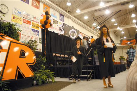 Having just received her diploma, senior Ashleigh Lynch smiles and poses for a photo near the stage.