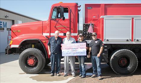 Standing with a check representing funds for new firefighting equipment for their new water tender truck, above, are from left: Fire Chief Gordon Gieser, District Board Chairman Fred Nelson, membership treasurer/secretary Jane Clapp and membership president Jeff Veach.
