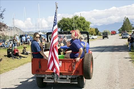 Participants in the Dayton Daze parade ride and display the flag.