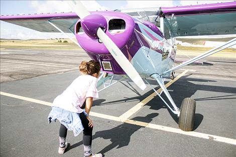 Youngster Olivia Ramirez takes a close-up look at the plane she called cotton candy because of its purple color.
