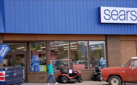 A customer exits Sears with a rake she purchased.