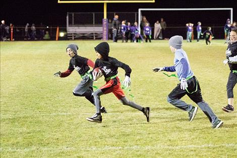 Youngsters race out for a quick game of flag football at halftime during the Polson Pirates' game Friday night.