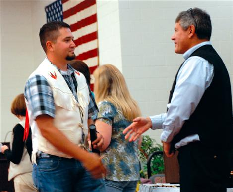 Brandon Gerrity, who earned a  Bachelor of Science degree in Forestry Wildland Fire, prepares to shake the hand of Confederated Salish and Kootenai Tribes Tribal Council Chairman Joe Durglo.