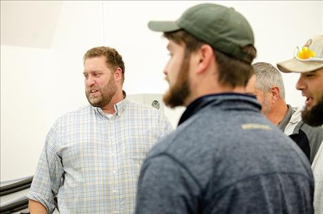 Sam Belanger, Green Ridge Biosolutions chief operations officer, (left) talks to farmers about hemp production.