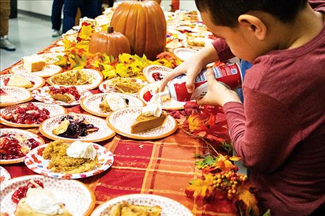 A young volunteer places the finishing touch on a piece of pumpkin pie.