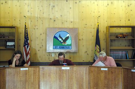 Members of the St. Ignatius City Council, from left, Marine Johnson,  Mayor Charlie Gariepy and Mack McConnell, discuss city business during the June 4 meeting.
