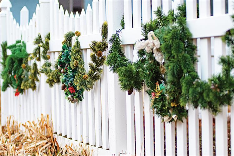 Decked out: Swags of holiday greenery adorn a white picket fence in Polson.