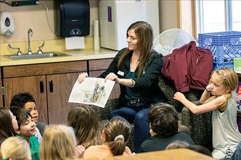 A cluster of  Linderman third graders gather around volunteer Megan Ahern as she reads a story about Dr. King.