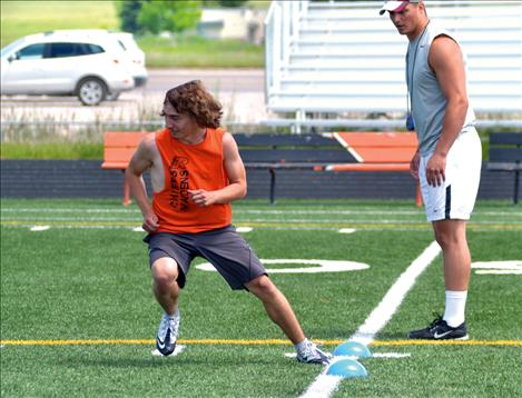 Ronan High School football player Ryan Talsma runs a drill with Griz player Jordan Tripp.