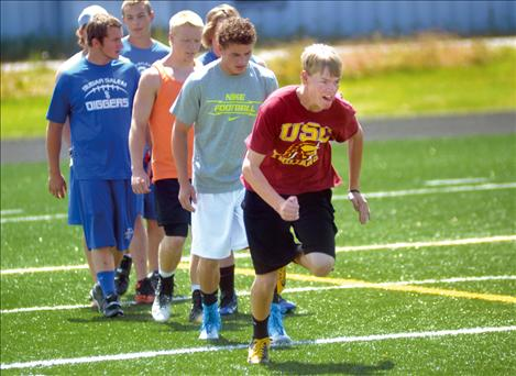 Football camp participants warm up with short sprints.