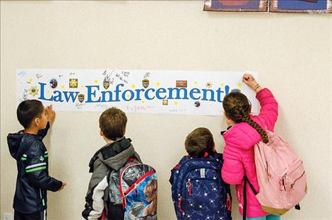 children sign their names to a banner that was later given to police officers to express appreciation for all the work they do.