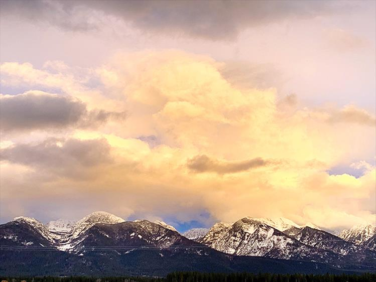 Evening light: Alpine glow and the clouds above illuminate snow-capped mountains east of Ronan on Feb. 23.