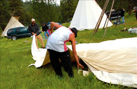 Cosmoe Harlow, foreground, and Chris Stikes fold up tepees as Culture Camp is dismantled.