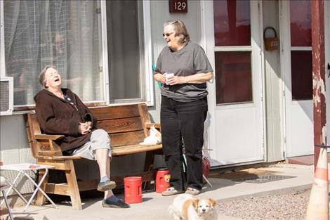 Neighbors  Pam  Robinson  and Laurie  Caswell  enjoy  a laugh  while  maintaining  social  distancing.