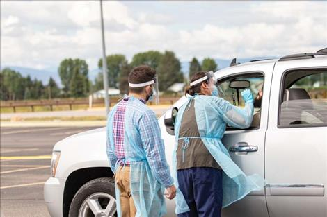 Rob Zolman / Valley Journal  A healthcare worker reaches into a car to do a nasal swab test during the drive-through COVID-19 testing event on Thursday in Pablo.