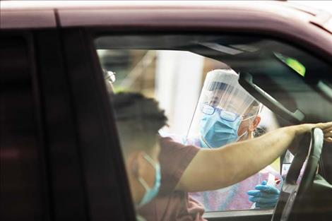 A swab test is  performed while the driver stays in  their vehicle.