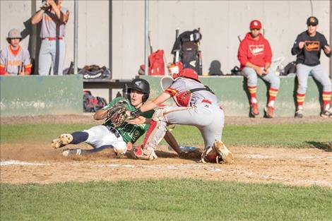 Mariner Ethan McCauley slips under the catcher's tag for a score.