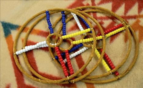 Hoops with beads roll and children can throw an arrow through the larger areas. When their skill improves, they aim for the tiny circle in the middle of the hoop.  Many Native games originally were a way of helping people improve skills, including hand eye coordination, hunting, throwing and quickness before going on a hunting trip.