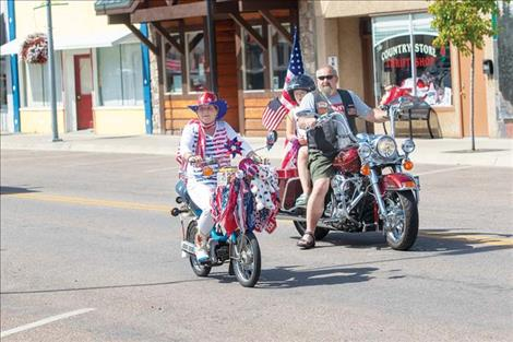 Folks  march down Main Street in Polson  to honor the flag.