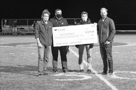 St. Luke Community Healthcare presents a donation to the PHS Athletic Department during halftime. Pictured above: Dr. Isaac Billings, PHS principal Andy Fors, Rob Alfiero, PA-C and  Dr. Tyler Thorson.