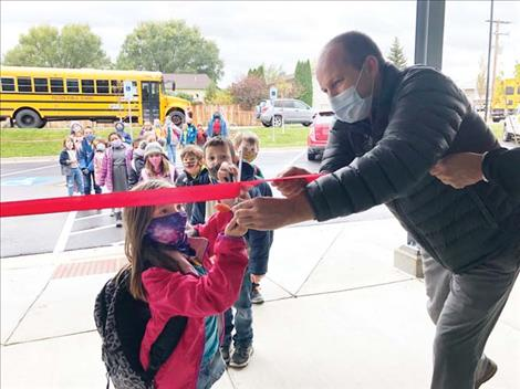 Aric Cooksley helps a youngster with the ribbon cutting at the new Polson club Monday.