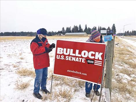 Lake County Democrats Craig McClure and Brody Moll dismantle political signs along U.S. Highway 93.