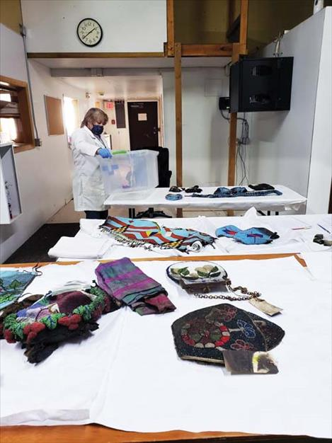 Conservator Nancy Fonicello examines items  recovered from the People's Center after the fire.  She reports that soot can be cleaned from many  of the items.