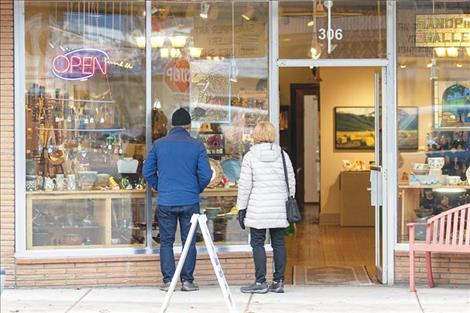 A couple Small Business Saturday shoppers take a  moment to do a little window shopping.