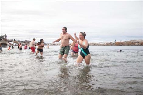 Polson Polar  Plunge participants enjoy the frigid water  on New Years Day. The  event was over quickly  but participants said it  was a good way to  bring in the year.